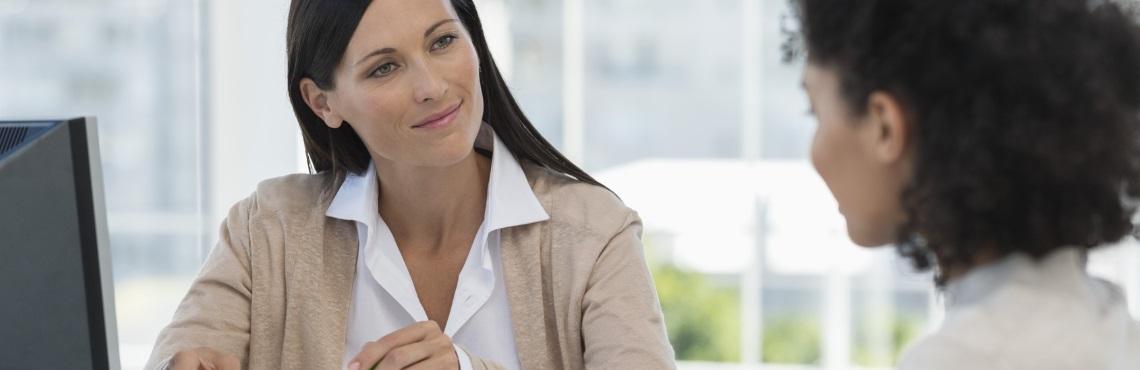 Dunkelhaarige Frau als Beraterin im Gespräch mit Frau mit gelockten Haaren