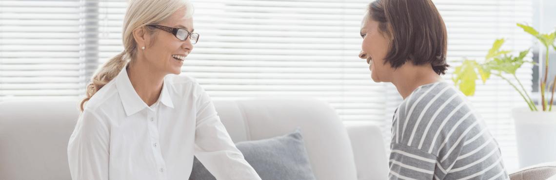 Ältere Dame mit weißer Bluse im Gespräch mit bünetter Frau