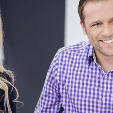 Blonde Frau und Mann im Karohemd haben ein Beratungsgespräch