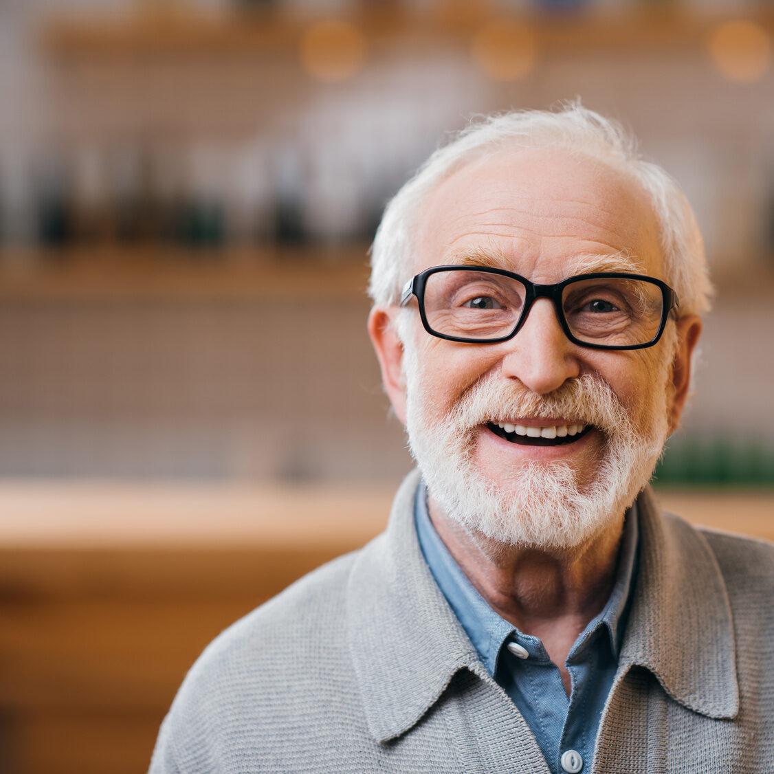 Glücklicher alter Mann mit Brille