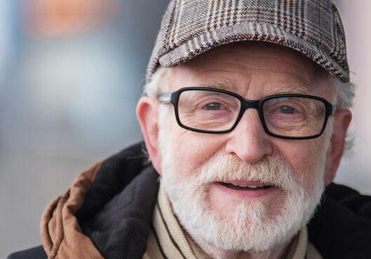 Älterer Mann mit kariertem Hut und Brille
