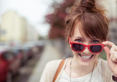 frau schaut lachend ber ihre rote sonnenbrille